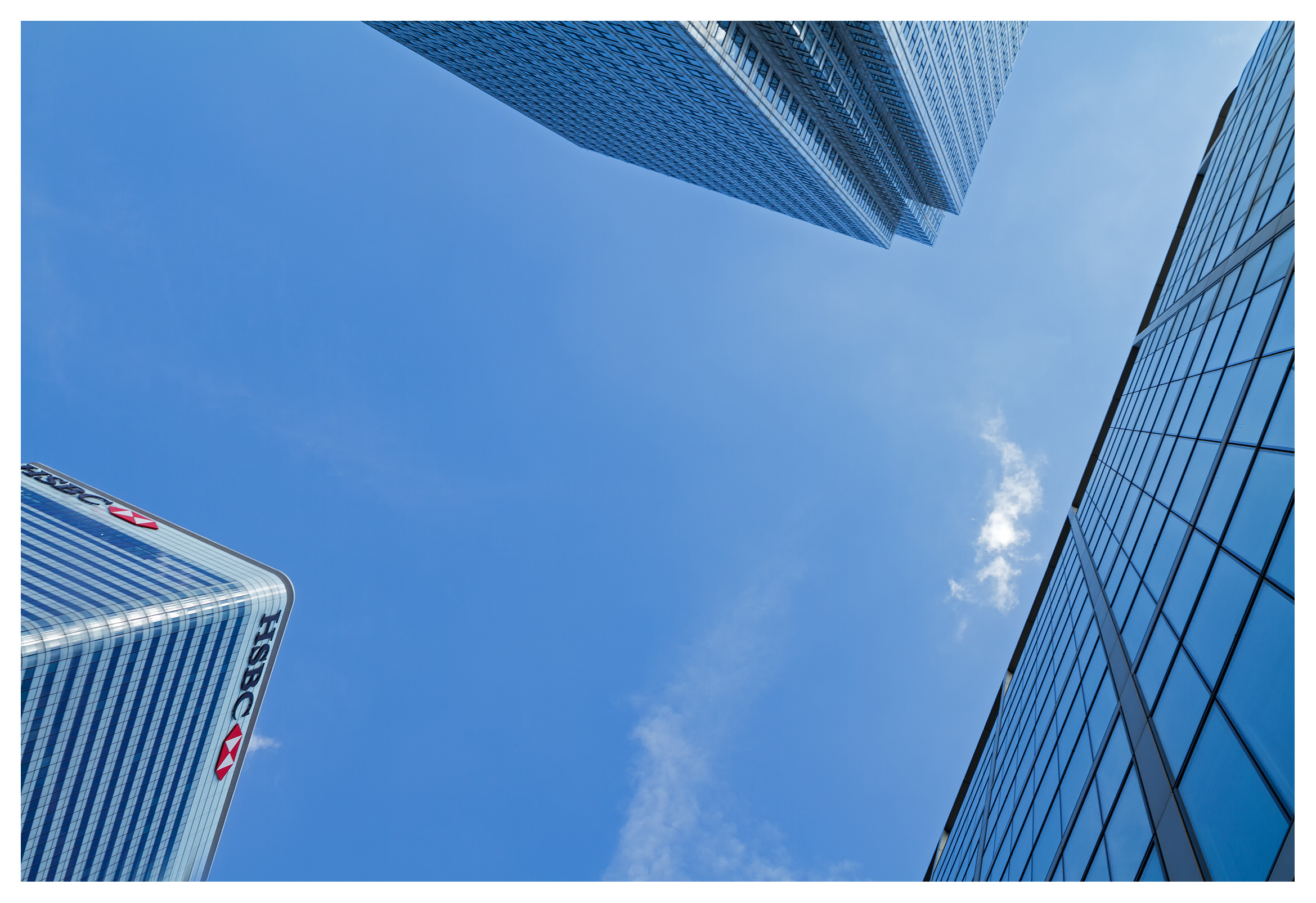 London commercial photography, Abstract business concept 'reach for the sky', Modern office buildings reaching up to a blue sky with a small white cloud overhead