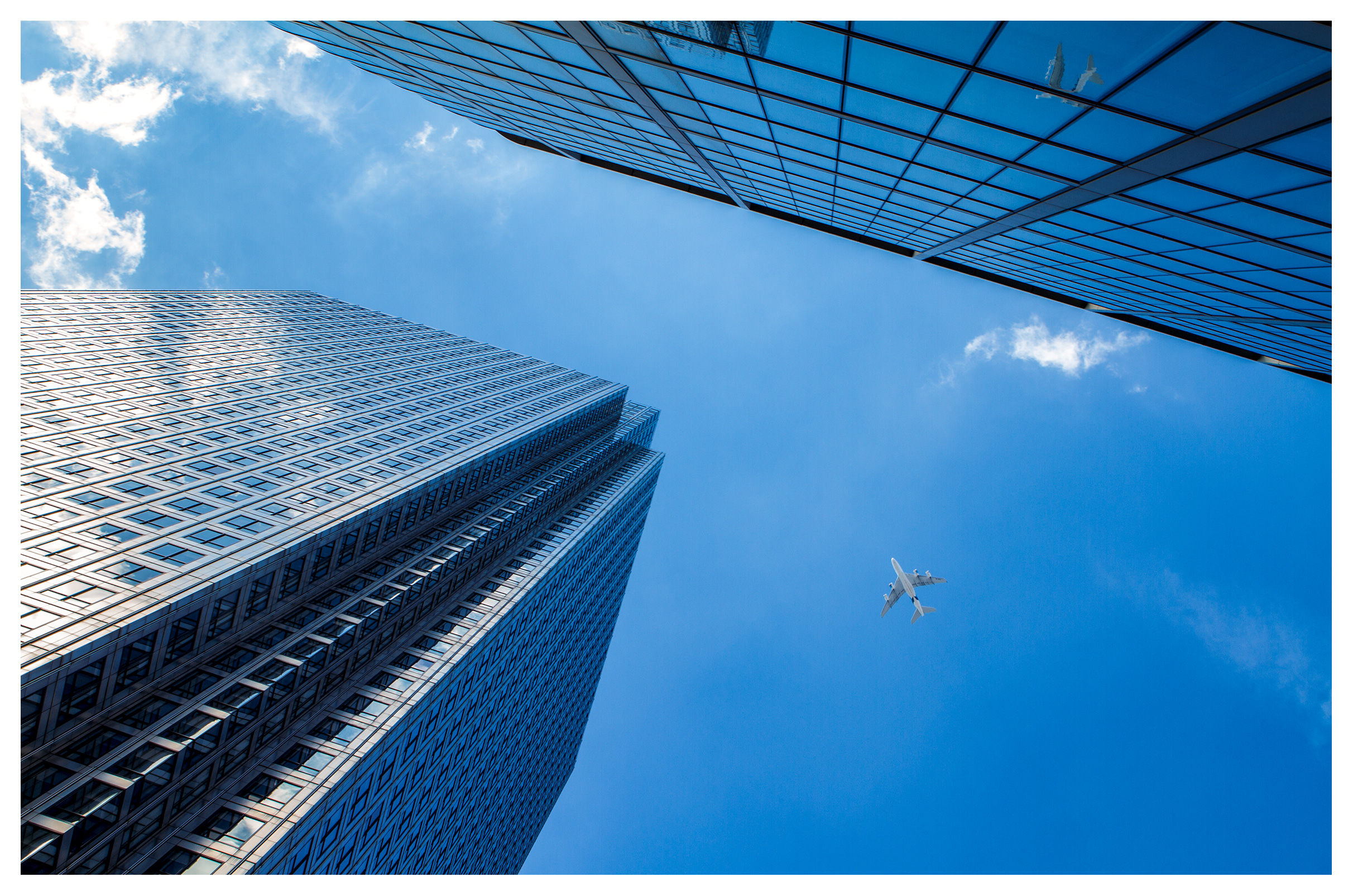 London commercial photography, Abstract business concept 'flying high' modern, sky-high office buildings, blue sky with commercial jet plane flying overhead
