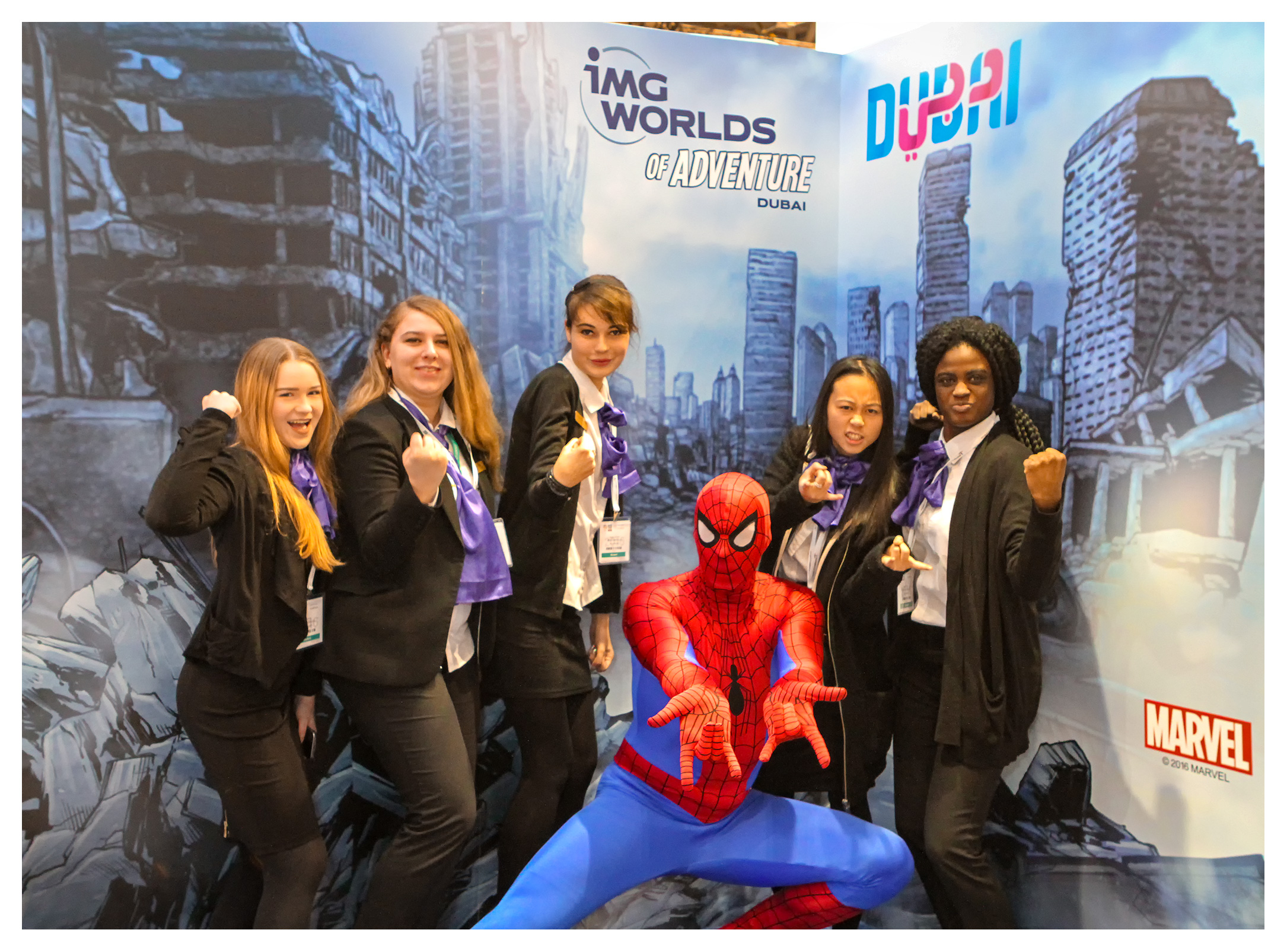 Exhibition photography. iMG Worlds stand: hospitality students posing with MARVEL hero Spiderman at the World Travel Market, ExCel, London 2016