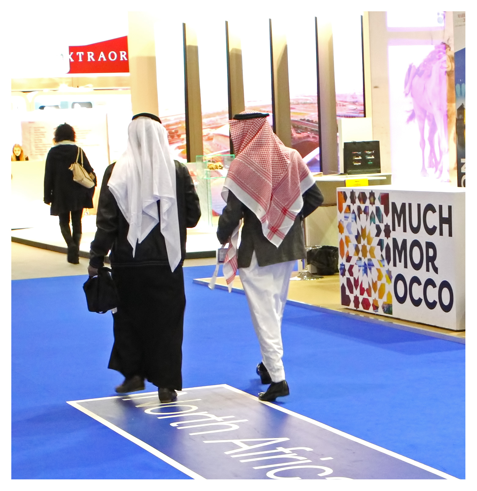 Exhibition photography: Arab businessmen in animated conversaton, World Travel Market 2017, ExCel London