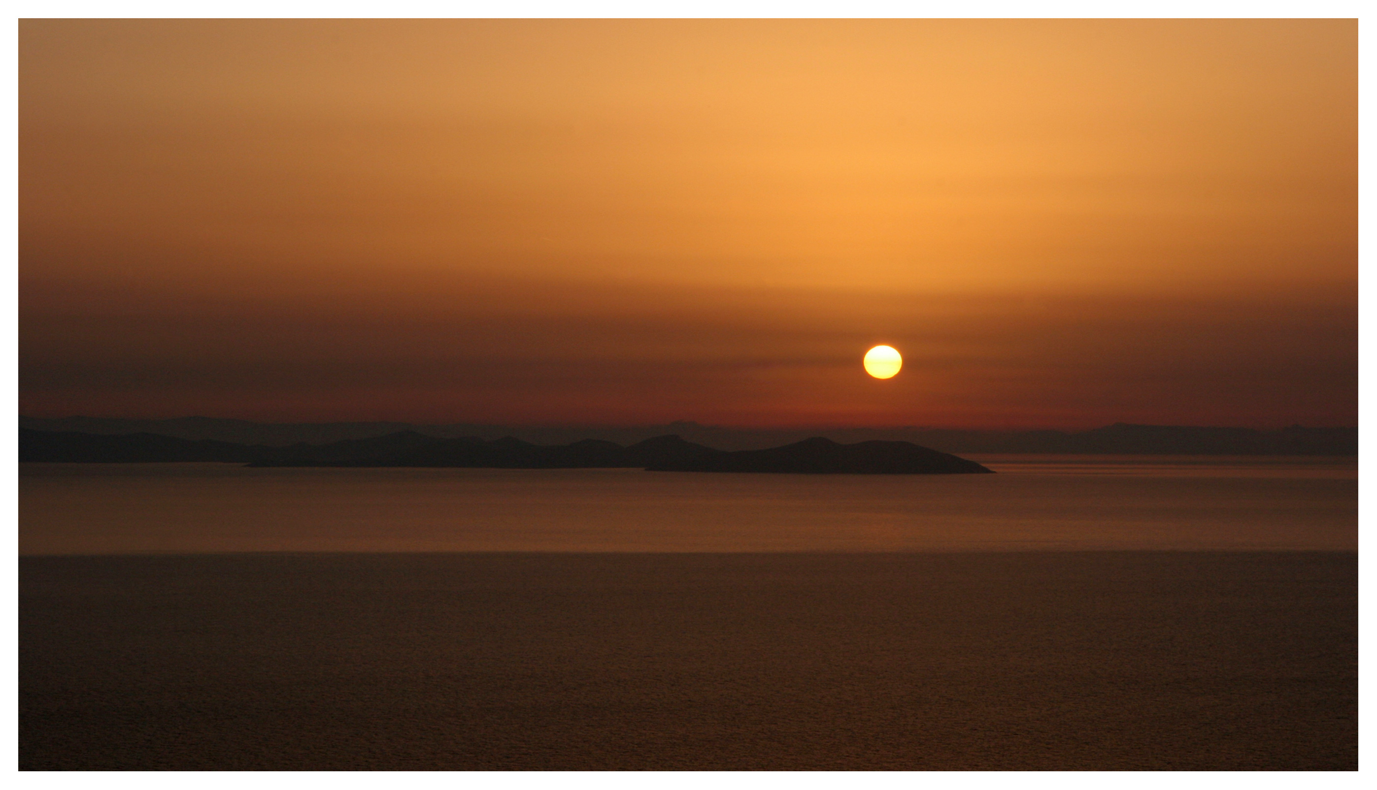 Yachting photography, Greek islands, Cyclades. Glorious sunrise at Sifnos looking eastwards to Antiparos and Paros