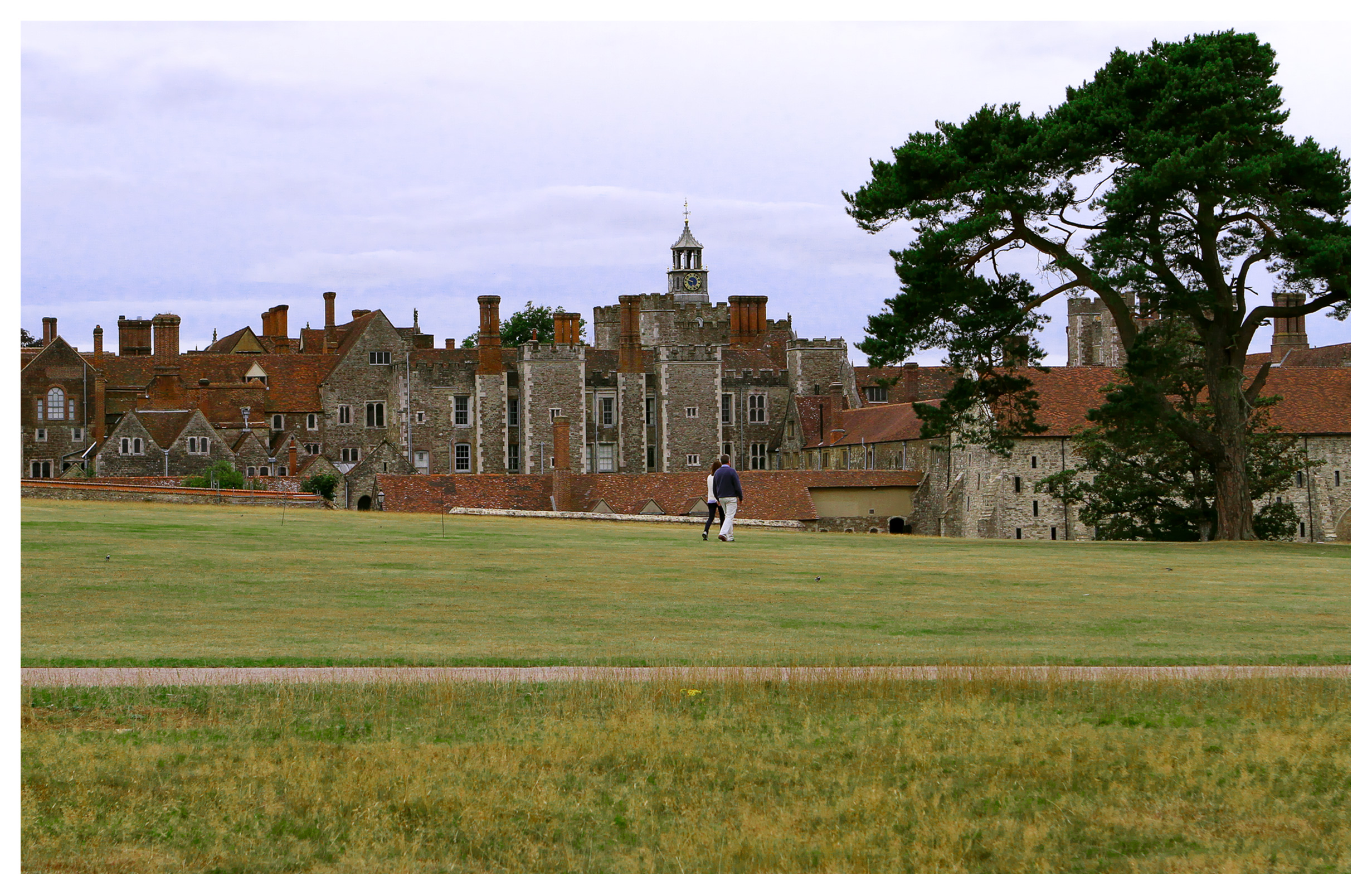 Couple walking on the grounds of Knole Park, Sevenoaks, Kent, England, with Knole House in the background