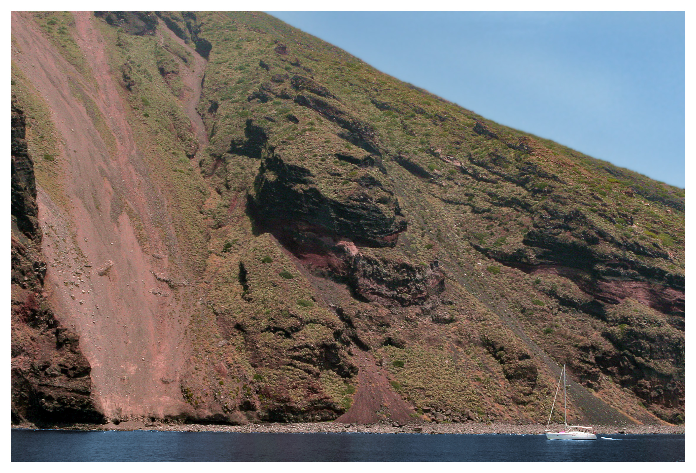 Yachting photography: A yacht sailing close to a towering volcanic hillside at Filicoudi, Aeolian Islands, Sicily