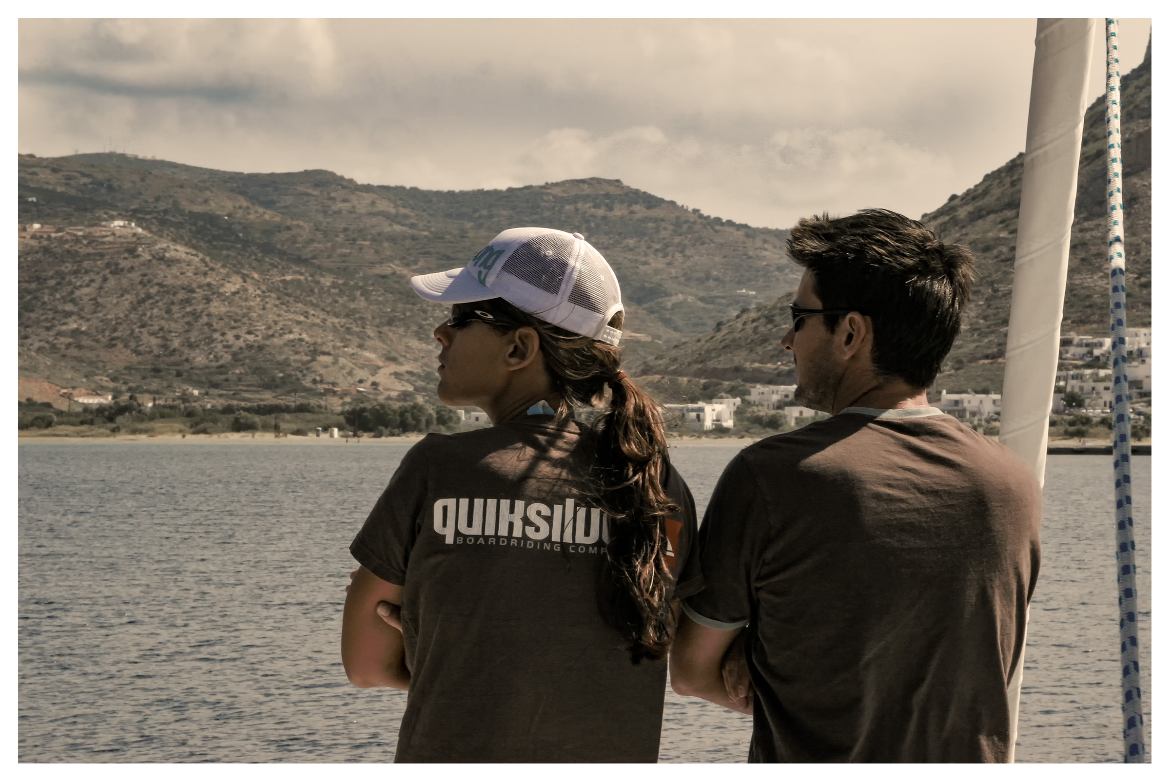 Yachting photography: couple taking in the views from a yacht arriving at Sifnos, Cyclades, Greece