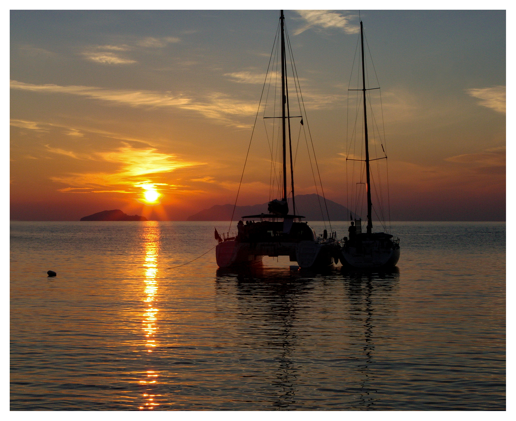Yachting photography: Monohull and catamaran anchored together in a glorious sunset near cape Sounio, Greece