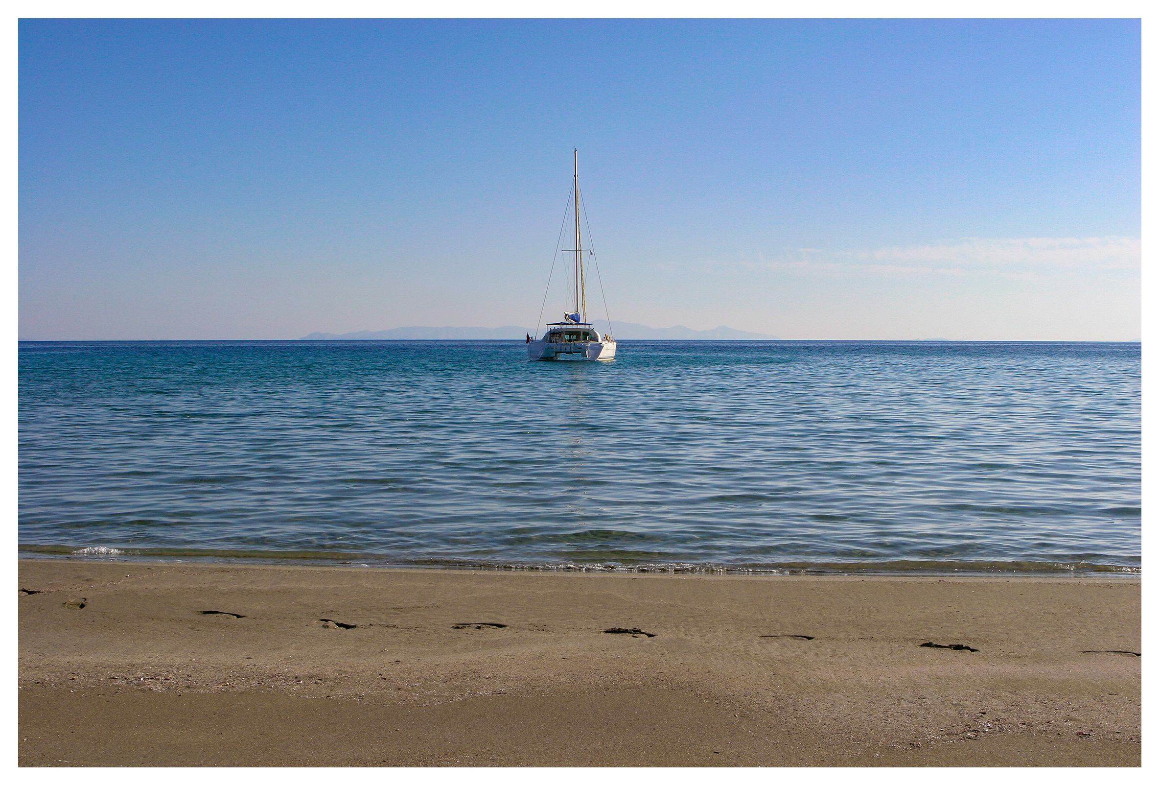 Yachting photography: A catamaran anchored off a desserted beach in Paros. Blue sky and a blue sea, Cyclades, Greece
