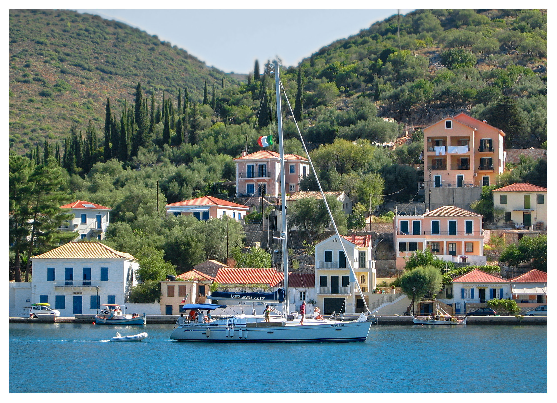 Yachting photography: A yacht passing by the seafront at Vathi town, Ithaka, Greece