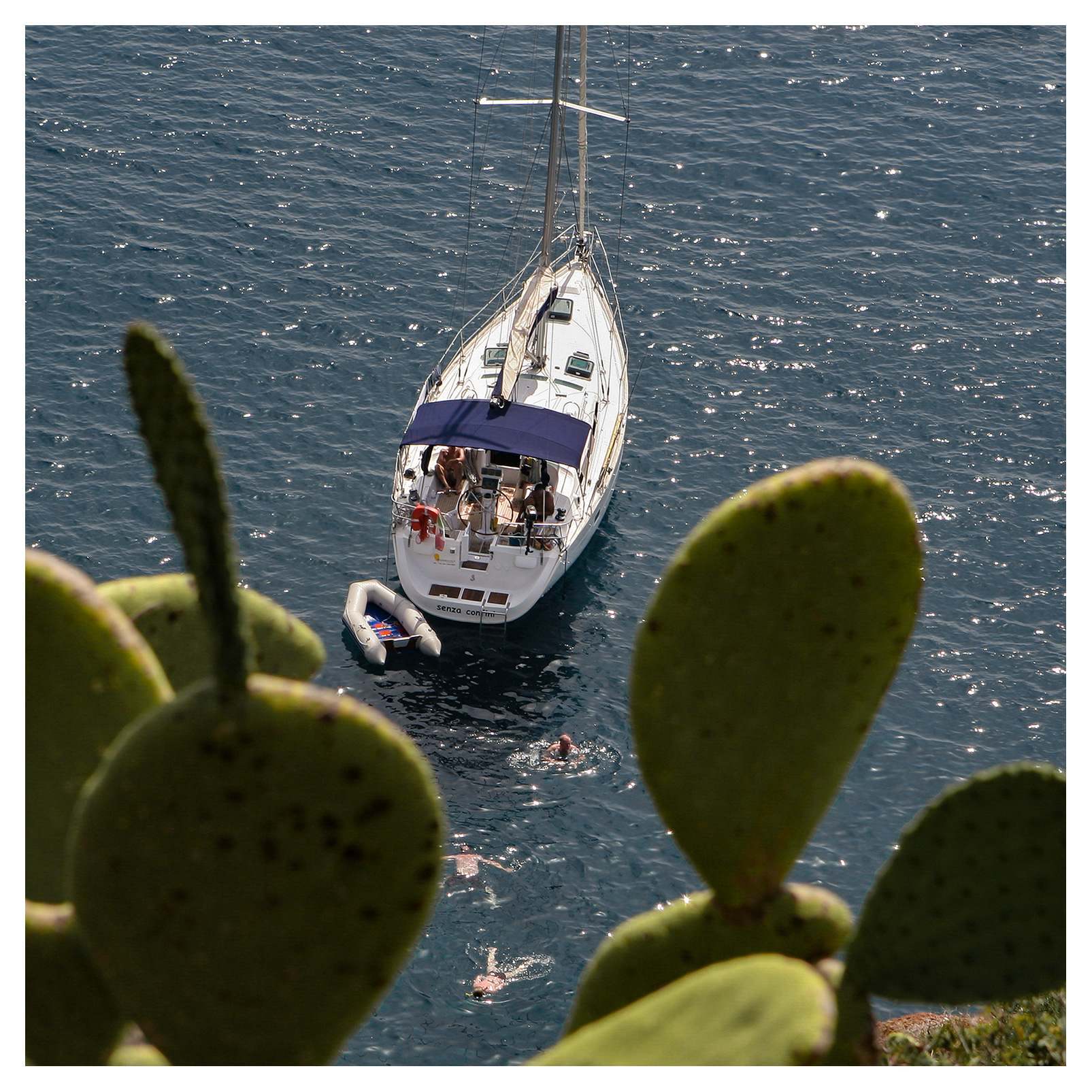 People swimming next to a sailing yacht anchored off Capo Milazzese, Panarea, Aeolian islands, Sicily