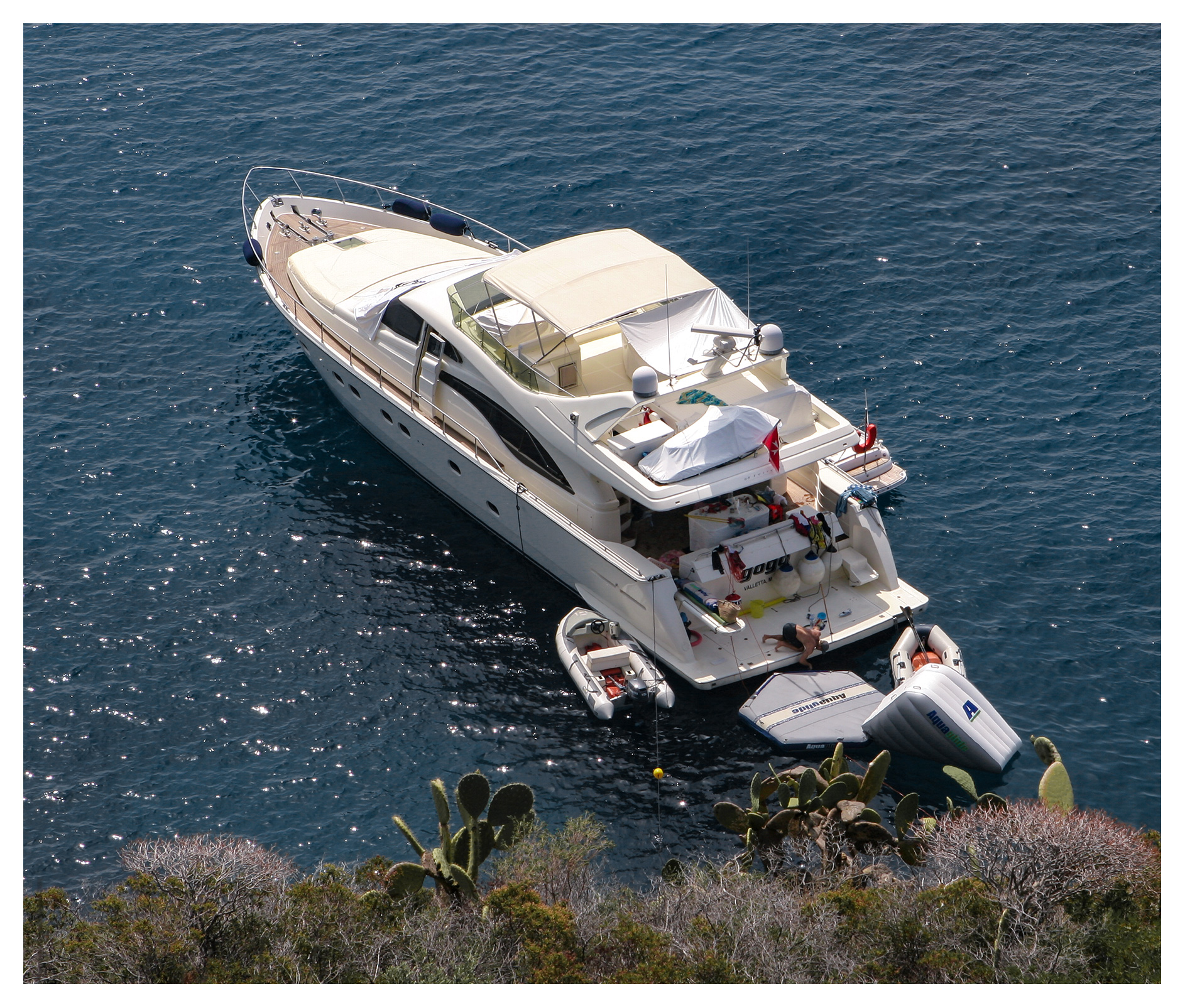 Skipper working on his motor yacht, anchored off Capo Milazzese, Panarea, Aeolian islands, Sicily