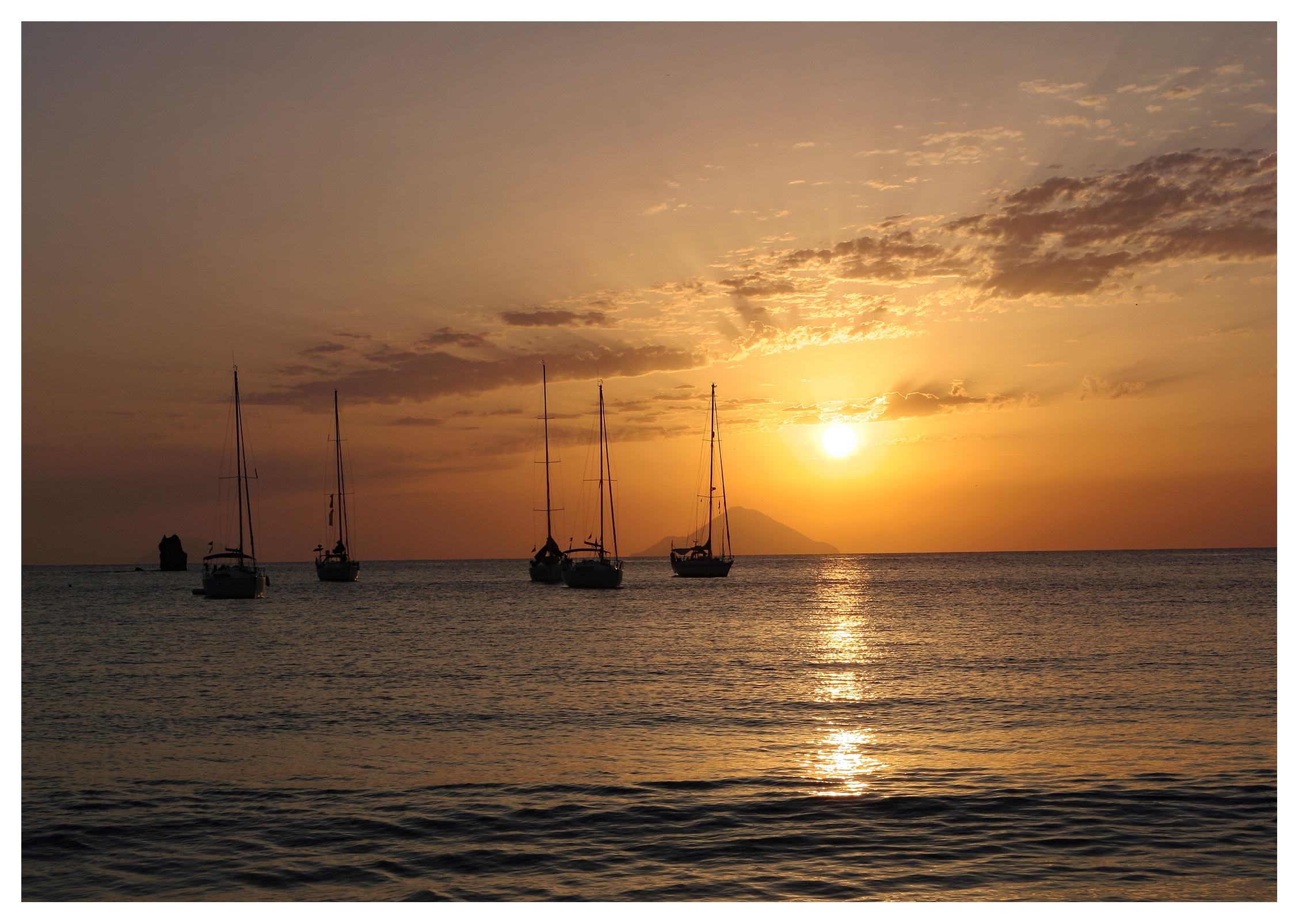 Yachting photography: Yachts anchored in a glorious sunset off Vulcano at the Aeolian Islands, Sicily