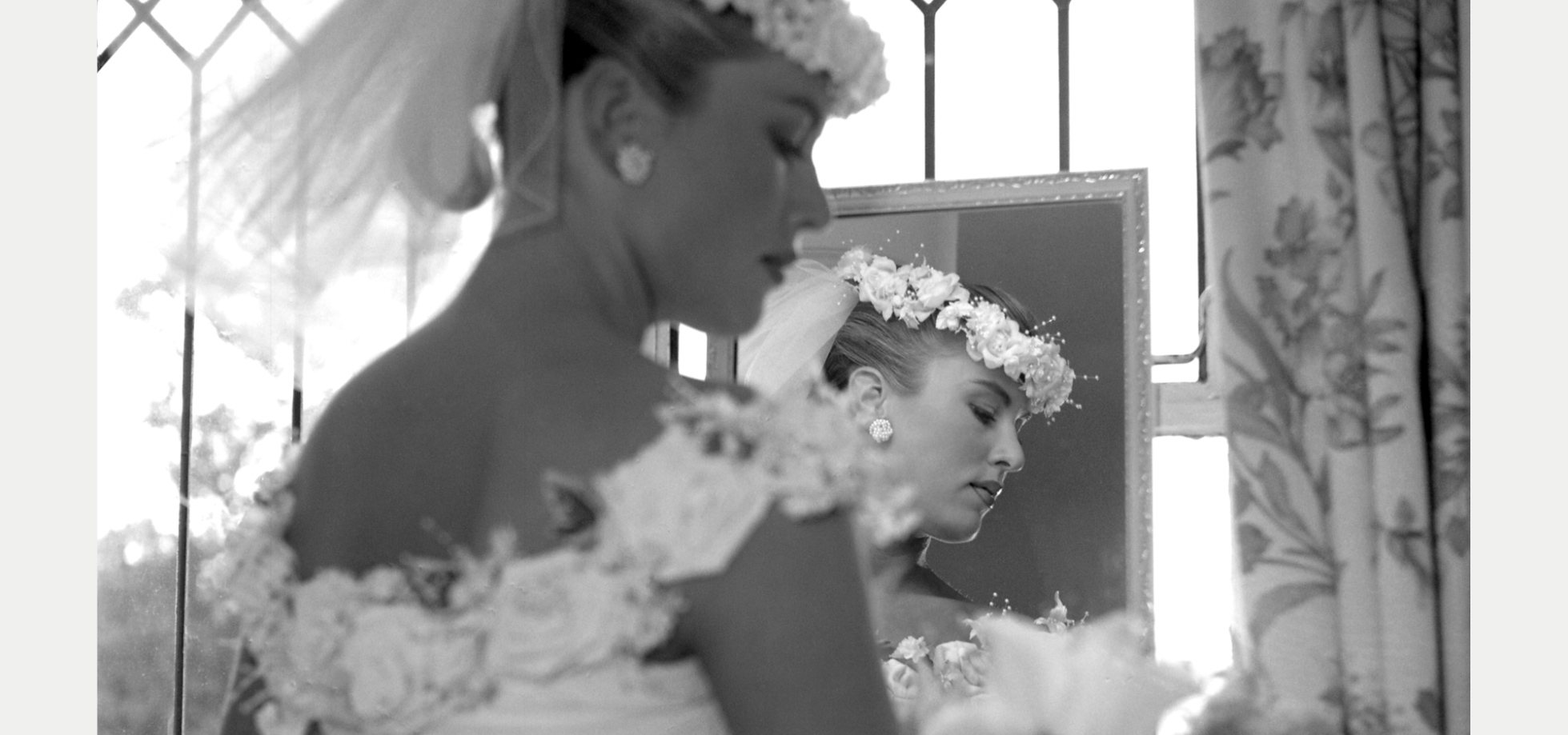 Bride with bouquet, mirror and window.